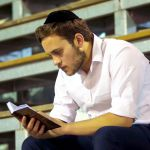 A Jewish man reads in the siddur (Jewish prayer book).
