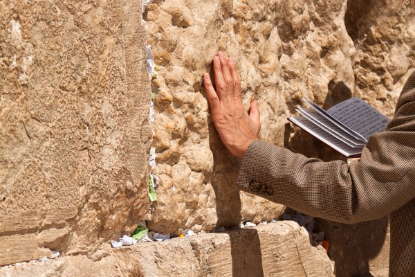 A man touches the Western (Wailing) Wall as he prays.