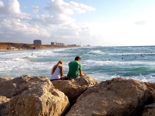 An Israeli couple sits by the Mediterranean Sea. (Photo by Ron Almog)