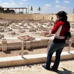 A woman examines a model of what the Temple Mount (upper left hand corner) and Jerusalem would have been like during the Second Temple period.