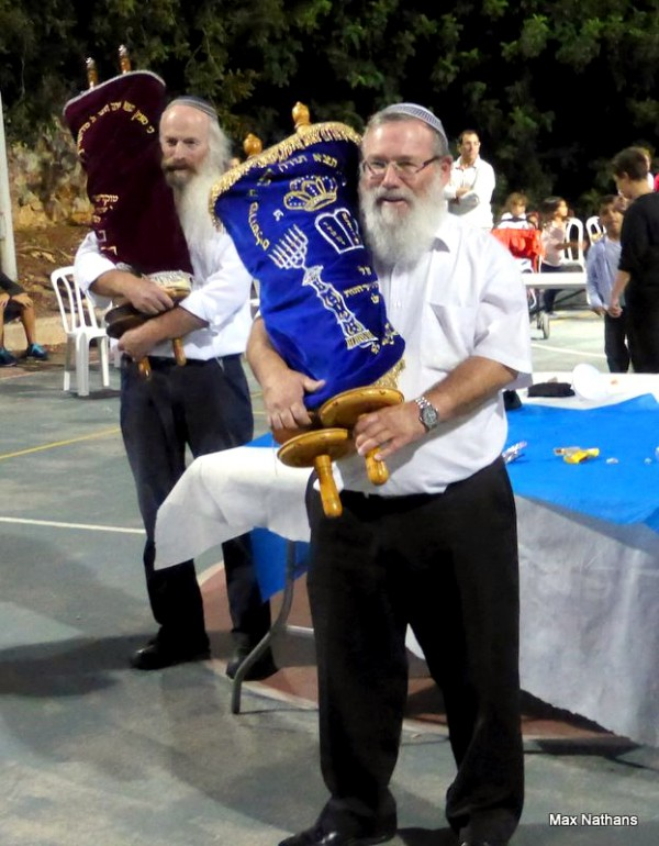 It is considered a mitzvah (good deed) to dance with the Torah and to rejoice over it on Simchat Torah. (Photo by Max@Nathans)