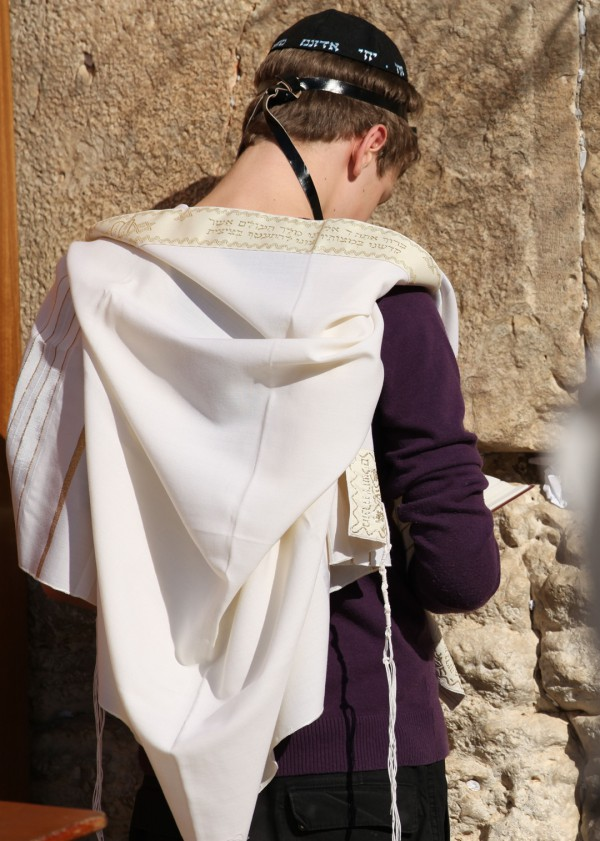 A Jewish teen wearing a tallit (prayer shawl), tefillin (phylacteries), and a kippah (head covering) prays at the Western (Wailing) Wall in Jerusalem. (Photo by the State of Israel)
