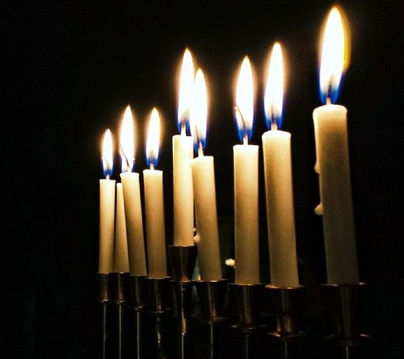 A fully lit Chanukah menorah glows in the darkness.  (Photo by Dima Barsky)