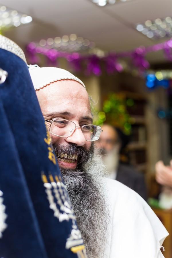 An Orthodox Jewish man embraces a Torah scroll.