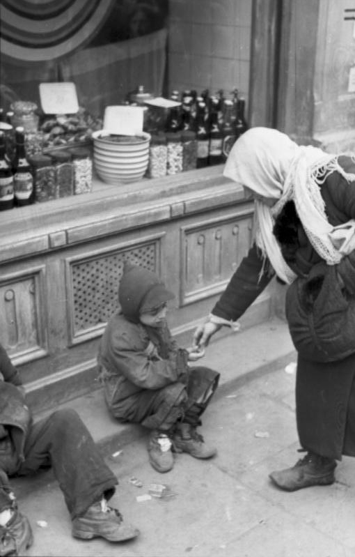 A woman in Poland's Warsaw Ghetto during the Holocaust helps a starving child.