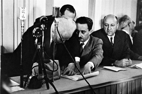 Ben Gurion signs Declaration of Independence, held by Moshe Sharet.