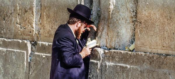 Jewish man reads from a siddur (Jewish prayer book) at the western (Wailing) Wall.