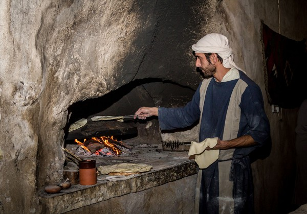 Man bakes bread at a recreated home in Nazareth, wearing period clothes from the time of Yeshua.