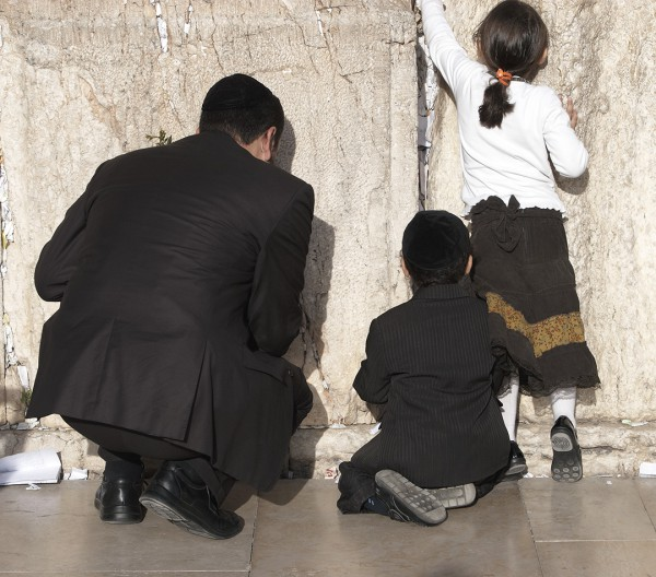 A father prays with his son and daughter at the Western (Wailing) Wall.