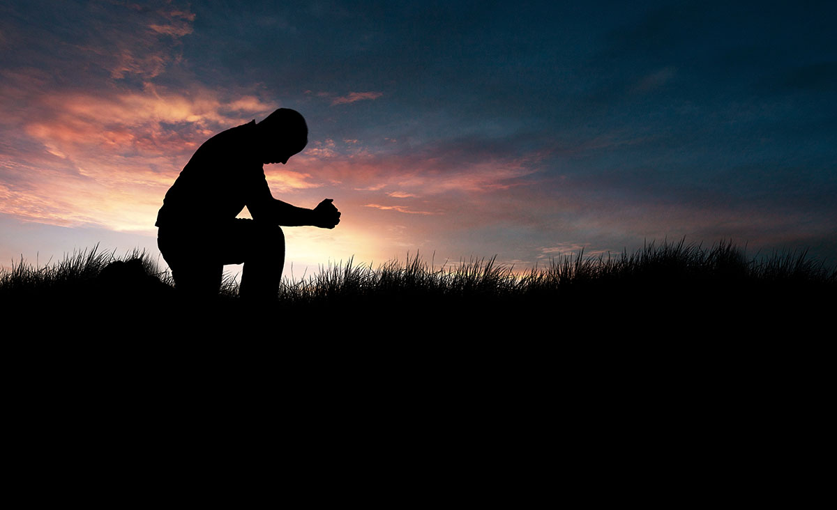 Man praying, kneeling