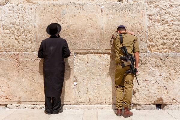Orthodox Jewish man and Israeli soldier pray at the Western (Wailing) Wall