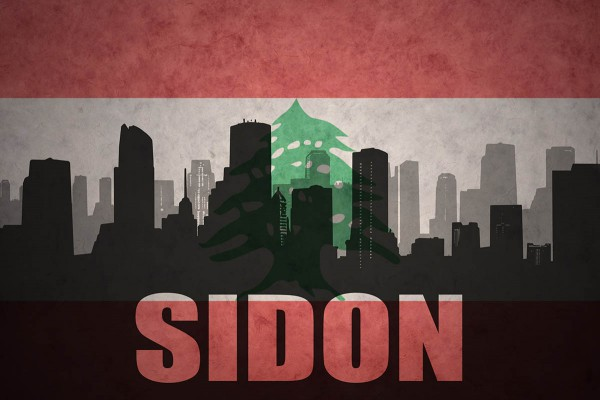 Silhoutte of Sidon skyline with flag of Lebanon in the background.