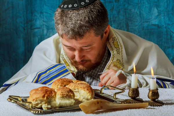 Jewish man prays a blessing over the challah (bread for Shabbat).