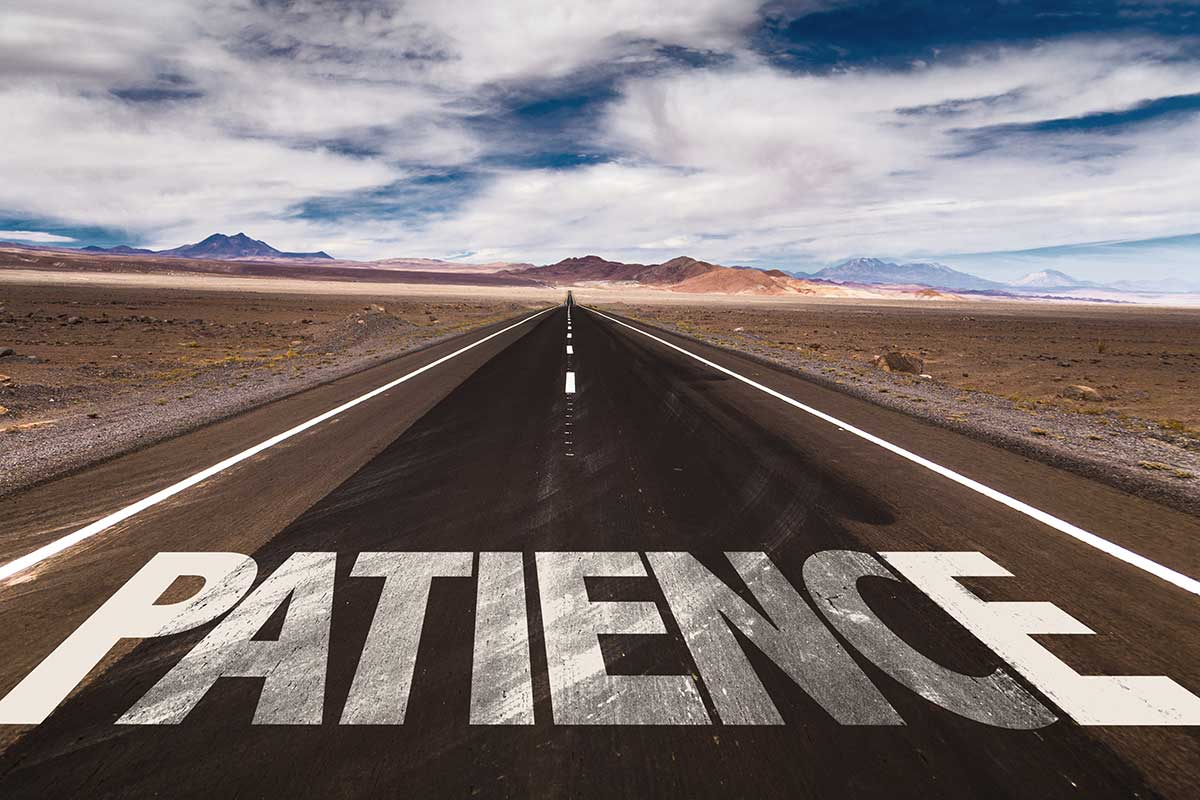 "The word ""patience"" is written on a road that goes through the desert."